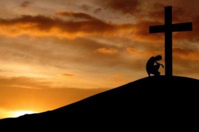 cross-man-praying-on-hill-big.jpg